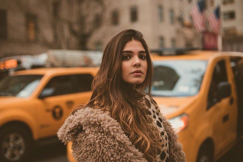 Młoda kobieta na tle żółtych taksówek