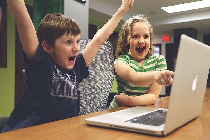 Wesołe dzieci przy laptopie